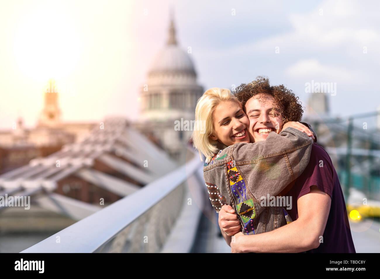 Happy couple hugging by Millennium bridge, River Thames, London. - Stock Image