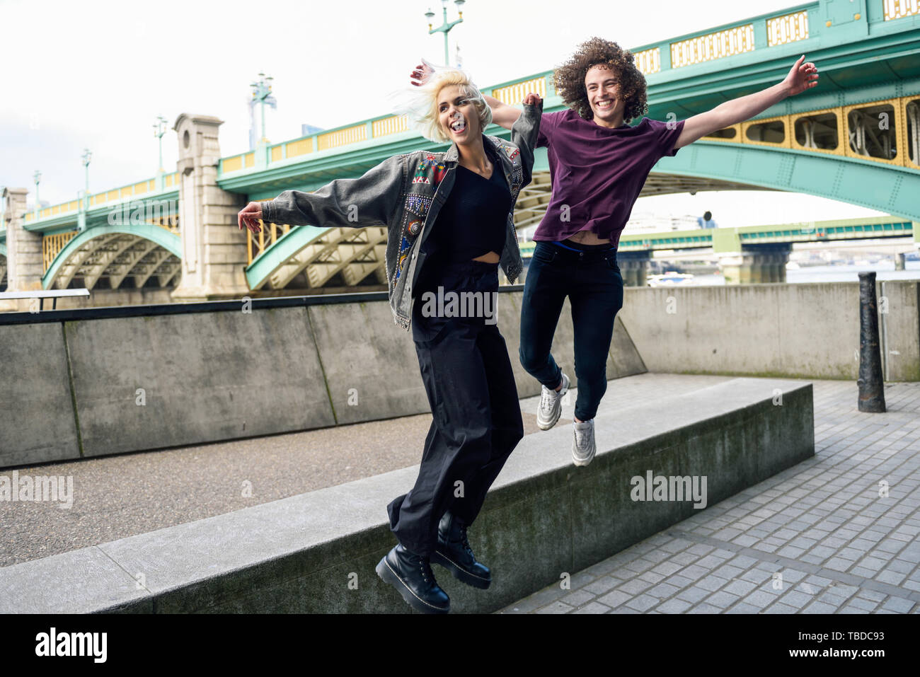 Funny couple junping near the Southwark bridge over River Thames, London - Stock Image
