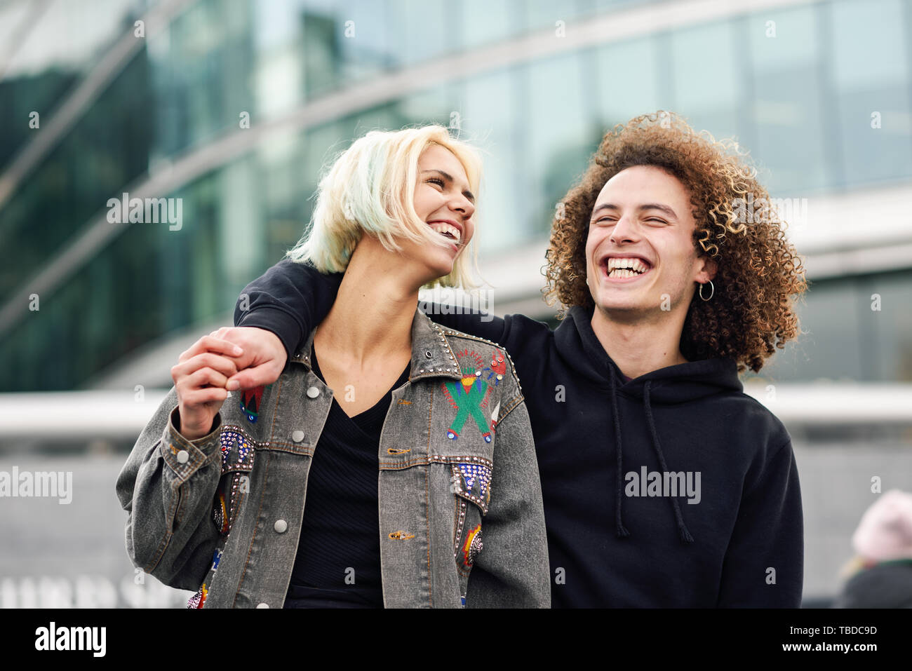 Happy young couple laughing in urban background - Stock Image