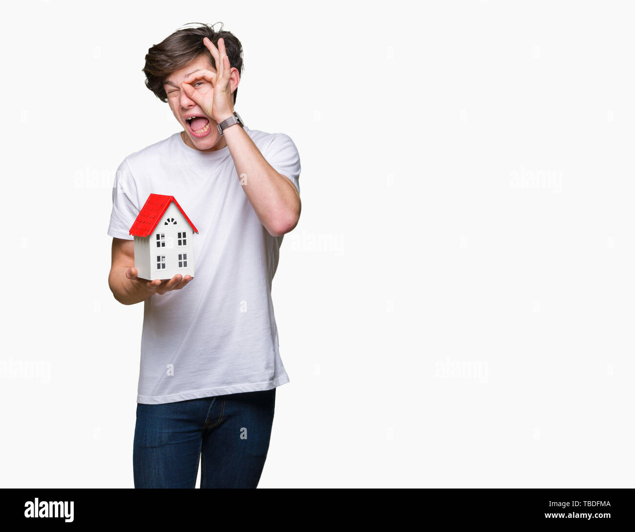 Young man holding house over isolated background with happy face smiling doing ok sign with hand on eye looking through fingers - Stock Image