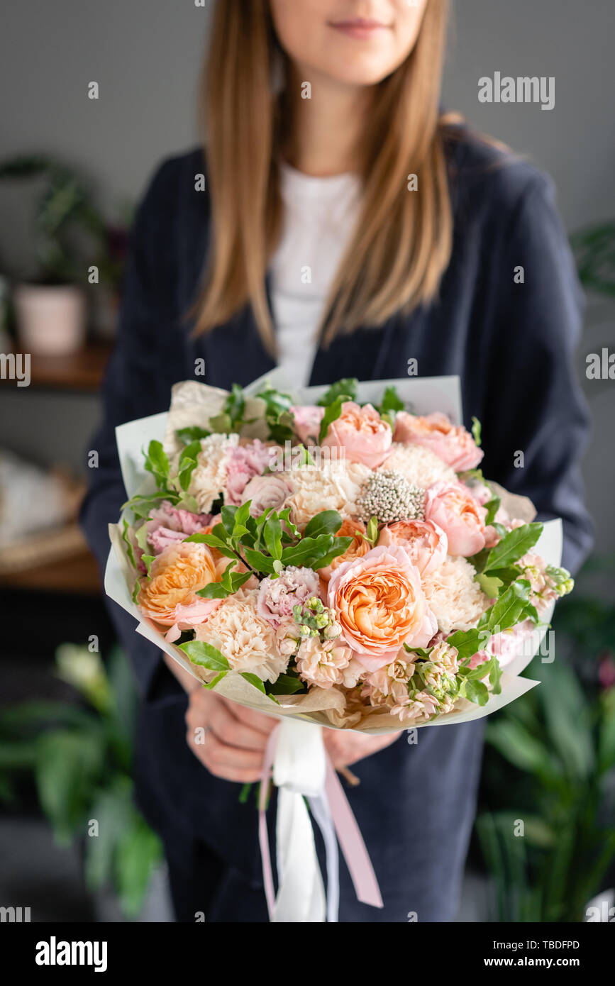 Small Beautiful bouquet of mixed flowers in woman hand. Floral shop concept . Beautiful fresh cut bouquet. Flowers delivery Stock Photo