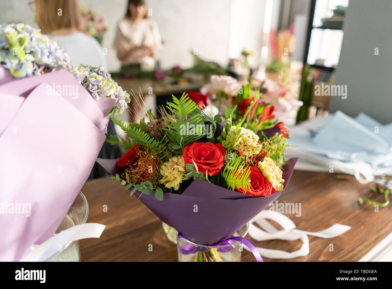 In the foreground a bouquet in a vase on the background of a flower shop. People work, Profession florist. Summer bouquet. Flowers delivery Stock Photo