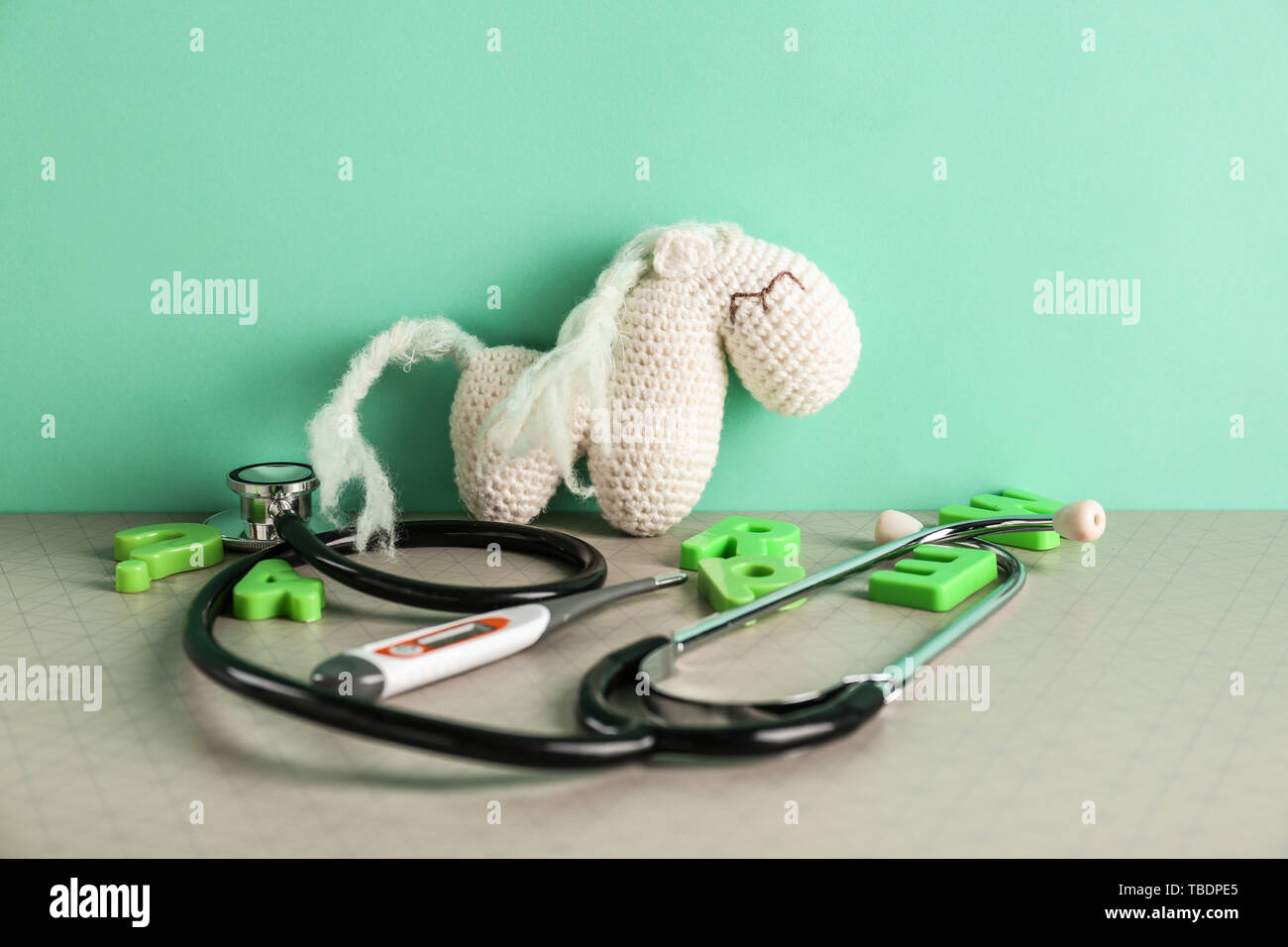 Stethoscope, thermometer and toy on table - Stock Image