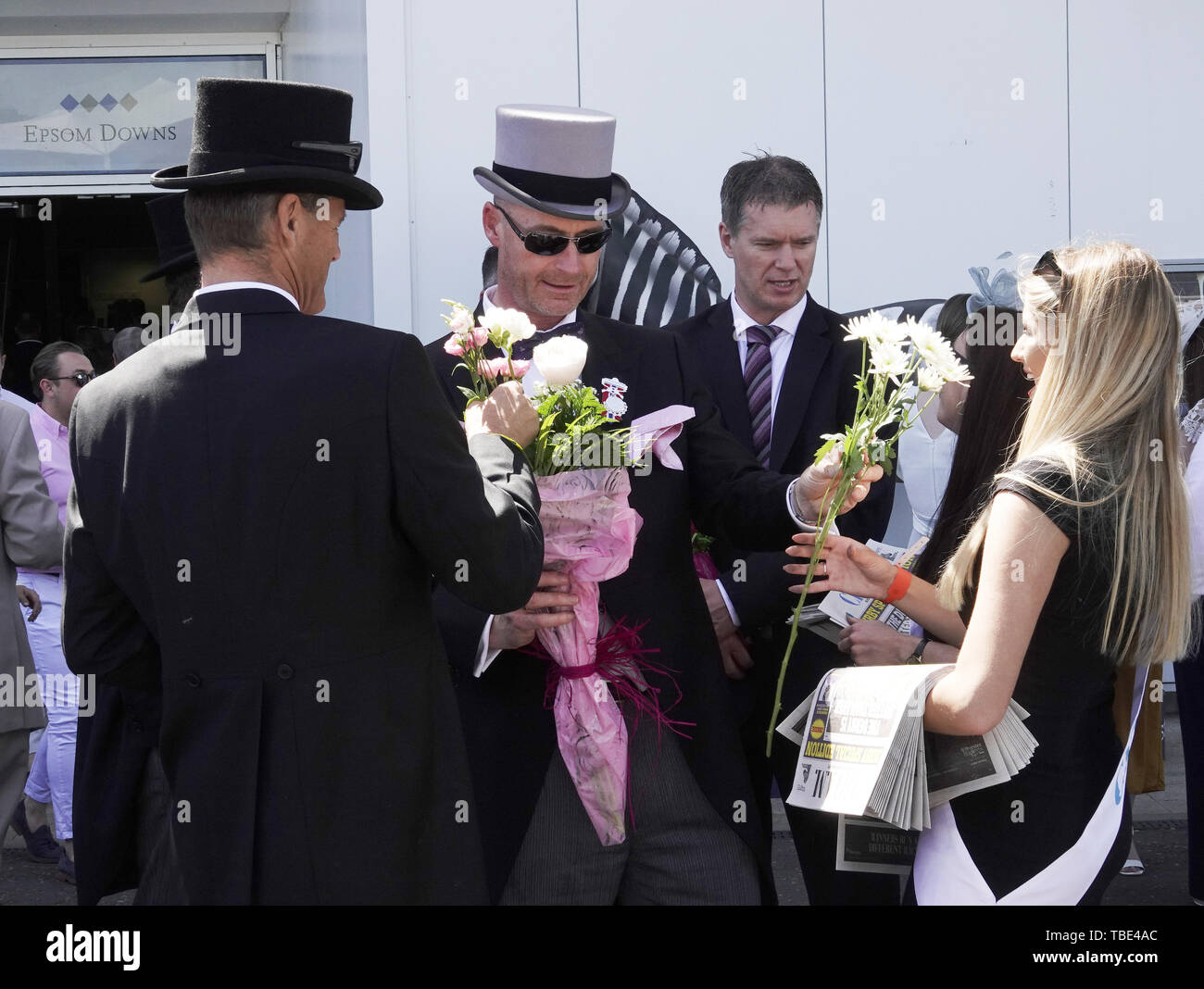 Epsom Downs, Surrey, UK. 1st June, 2019. The girls garlanded with flowers by ttentive gentlemen on arrival on Derby day at the world famous Investec Derby Festival Credit: Motofoto/Alamy Live News - Stock Image