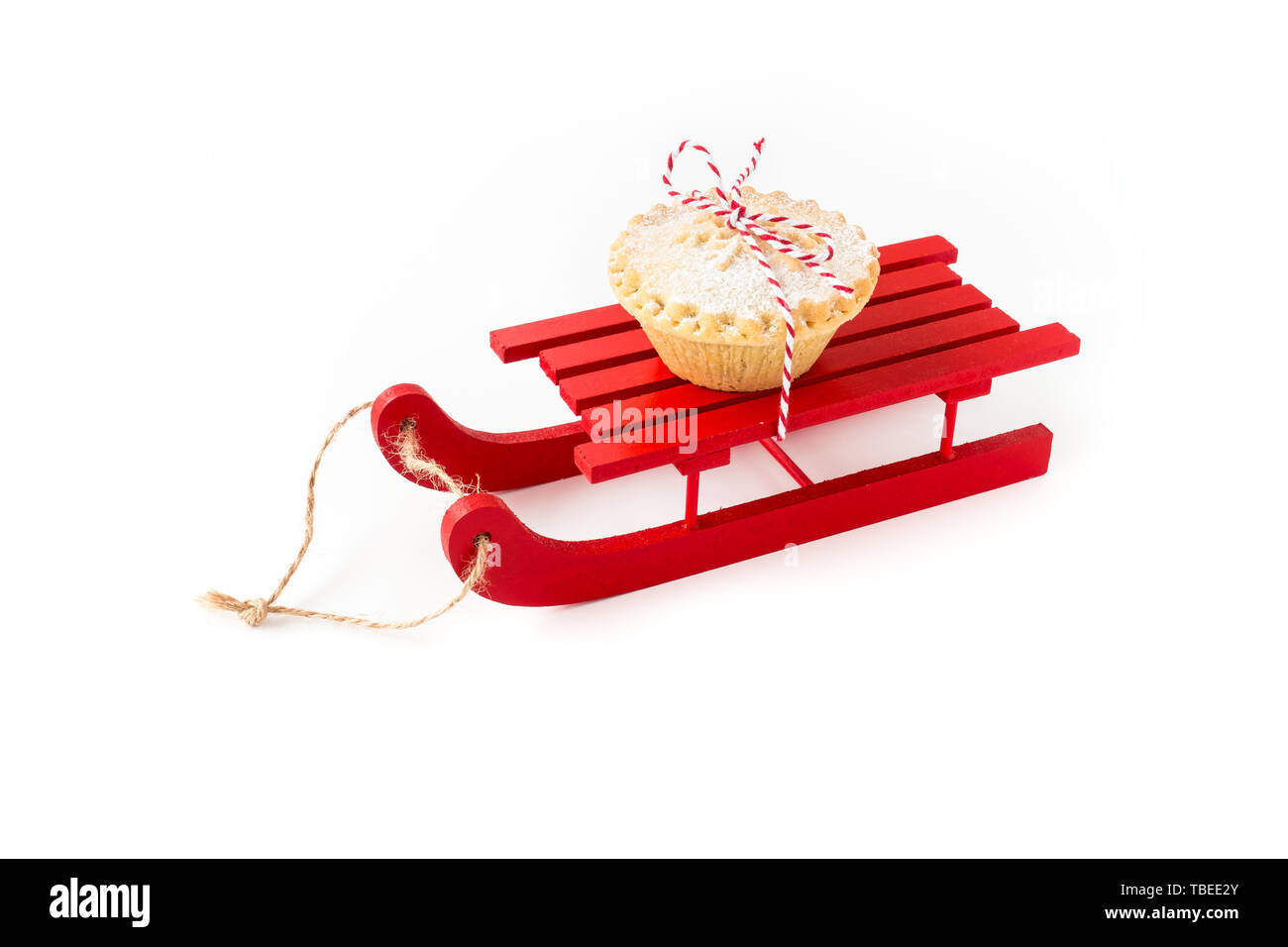 Red wooden sledge with Mince Pie isolated on white background. Angled view. - Stock Image