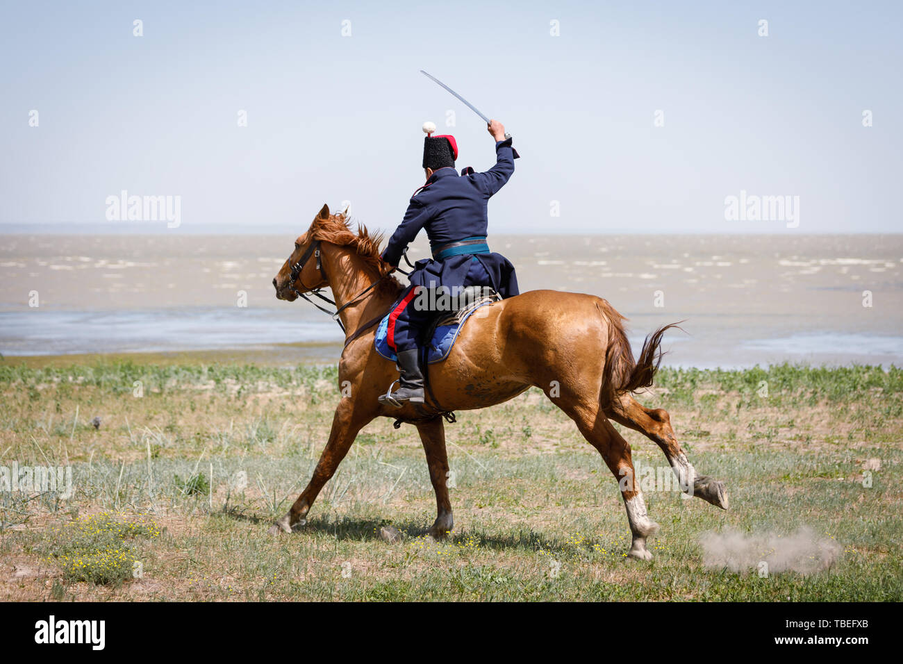 Horseman in blue military clothes riding along the seashore with a sabre in his hand - Stock Image