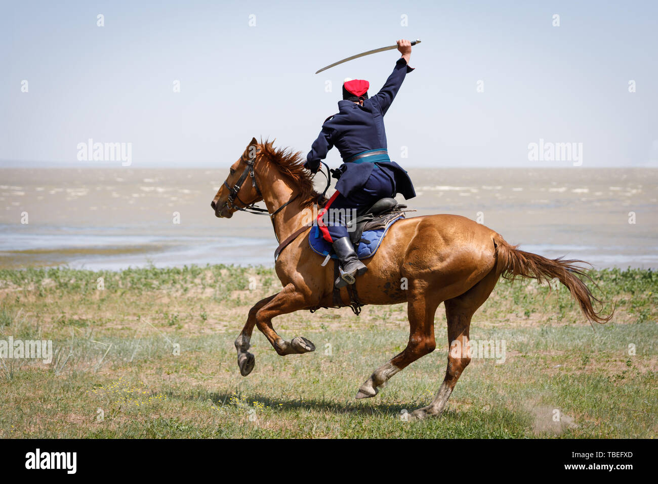 Don Cossack fast rides along the seashore on a horse with a sabre in his hand - Stock Image