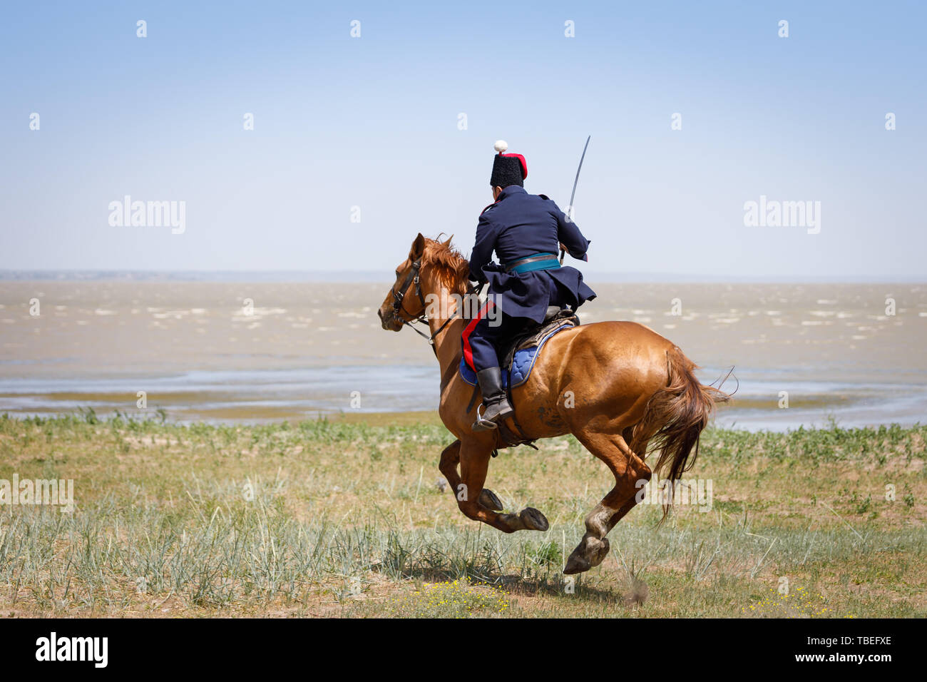 Don Cossack in blue military clothes quickly rides along the coast of the sea with a sabre in his hand - Stock Image
