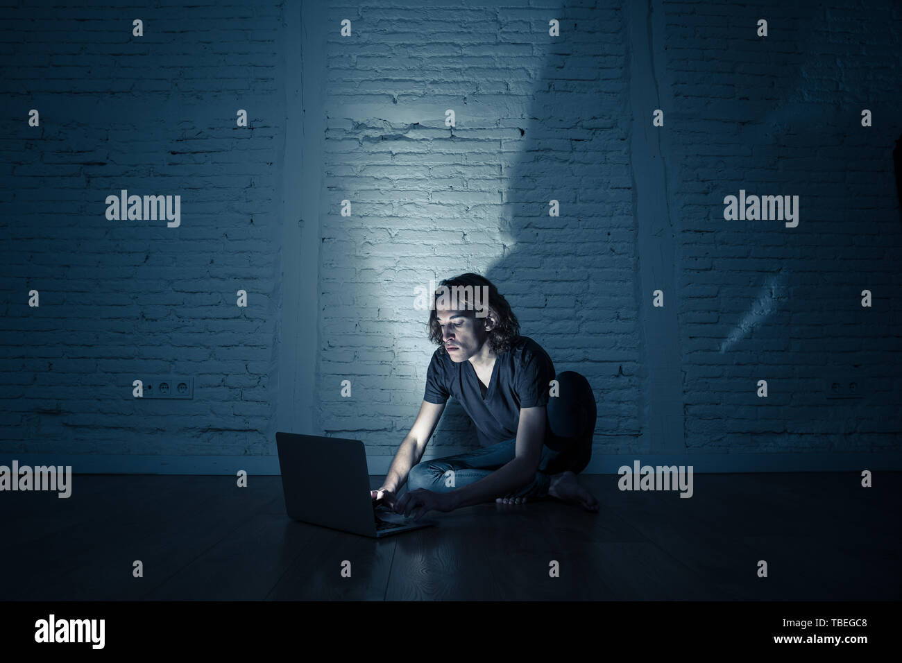 Severely distraught young teen man with laptop suffering cyberbullying and harassment being online abused by stalker or gossip feeling desperate and h - Stock Image