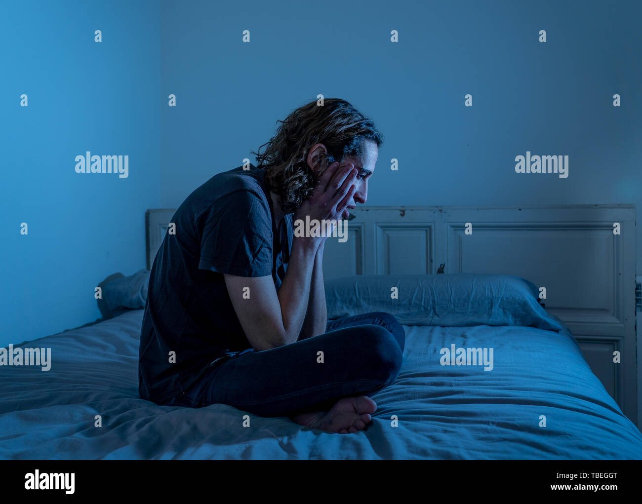 Devastated millennial man crying sad feeling hurt and hopeless suffering Depression. Depressed teenager victim of bullying or abuse sitting on bed alo Stock Photo