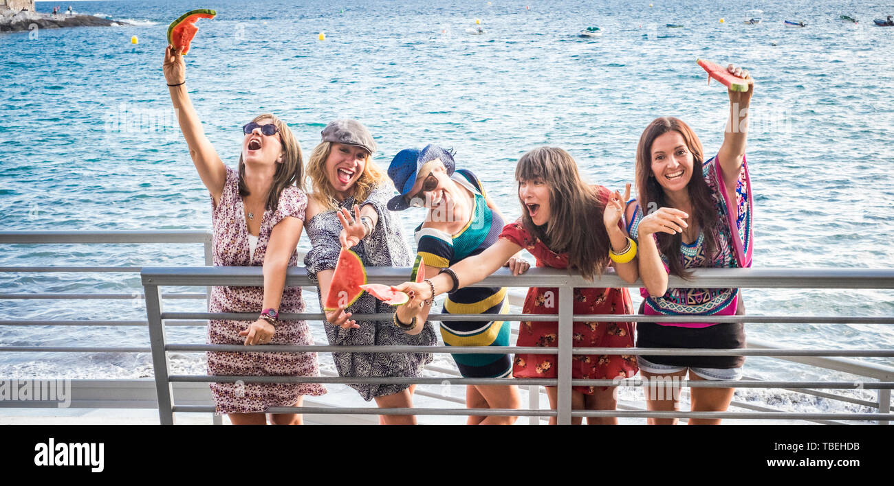 Group of crazy females friends have fun outdoor with watermelon and friendship - people on vacation enjoy and laugh a lot with joyful together - blue  Stock Photo