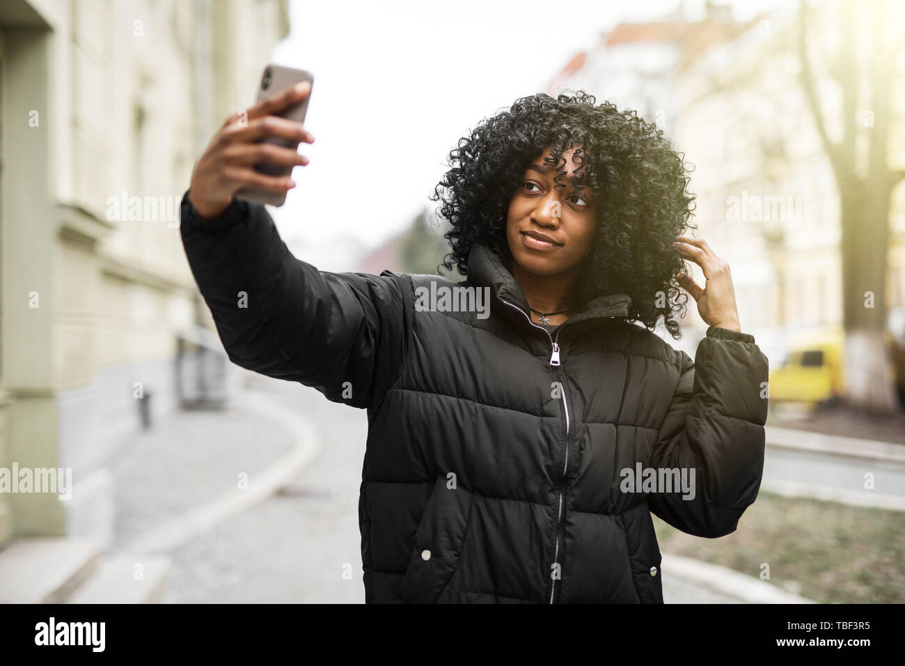 Cheerful young african woman wearing coat walking outdoors, taking a selfie Stock Photo