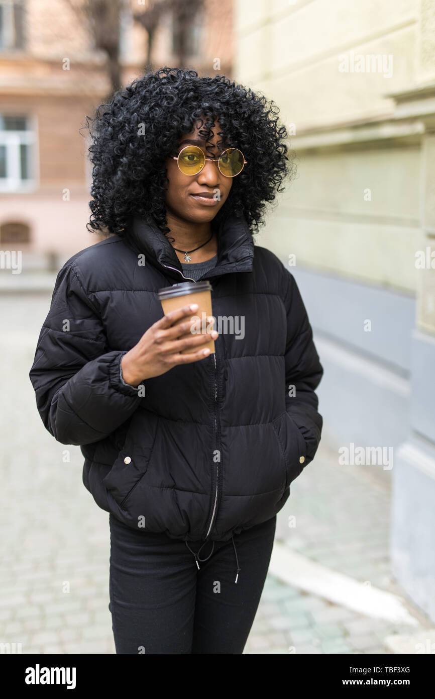 Cheerful young african woman wearing coat walking outdoors, holding takeaway coffee cup Stock Photo