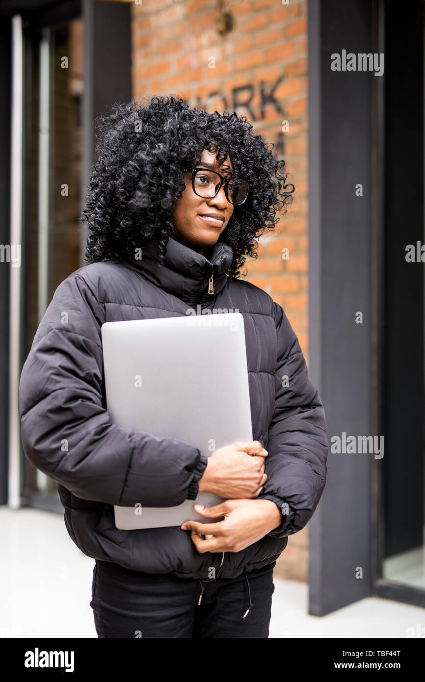 Young woman on the street working on laptop and talking on mobile phone. Stock Photo