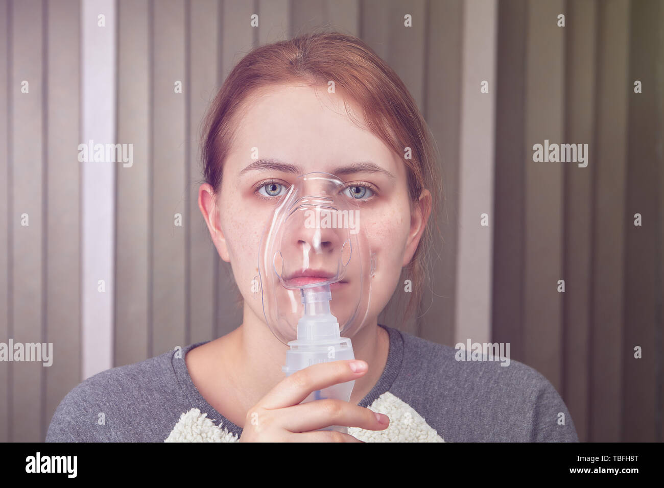 Young woman is breathing with help of nebulizer mask, because she has chronic obstructive pulmonary disease. - Stock Image
