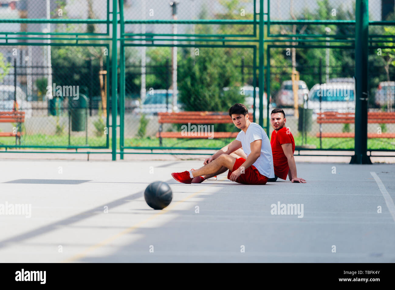 Two Friends After A Long Hard Basketball Game Have Some Rest On The Basketball Court Sitting Next To Each Other And Have A Conversation Stock Photo Alamy