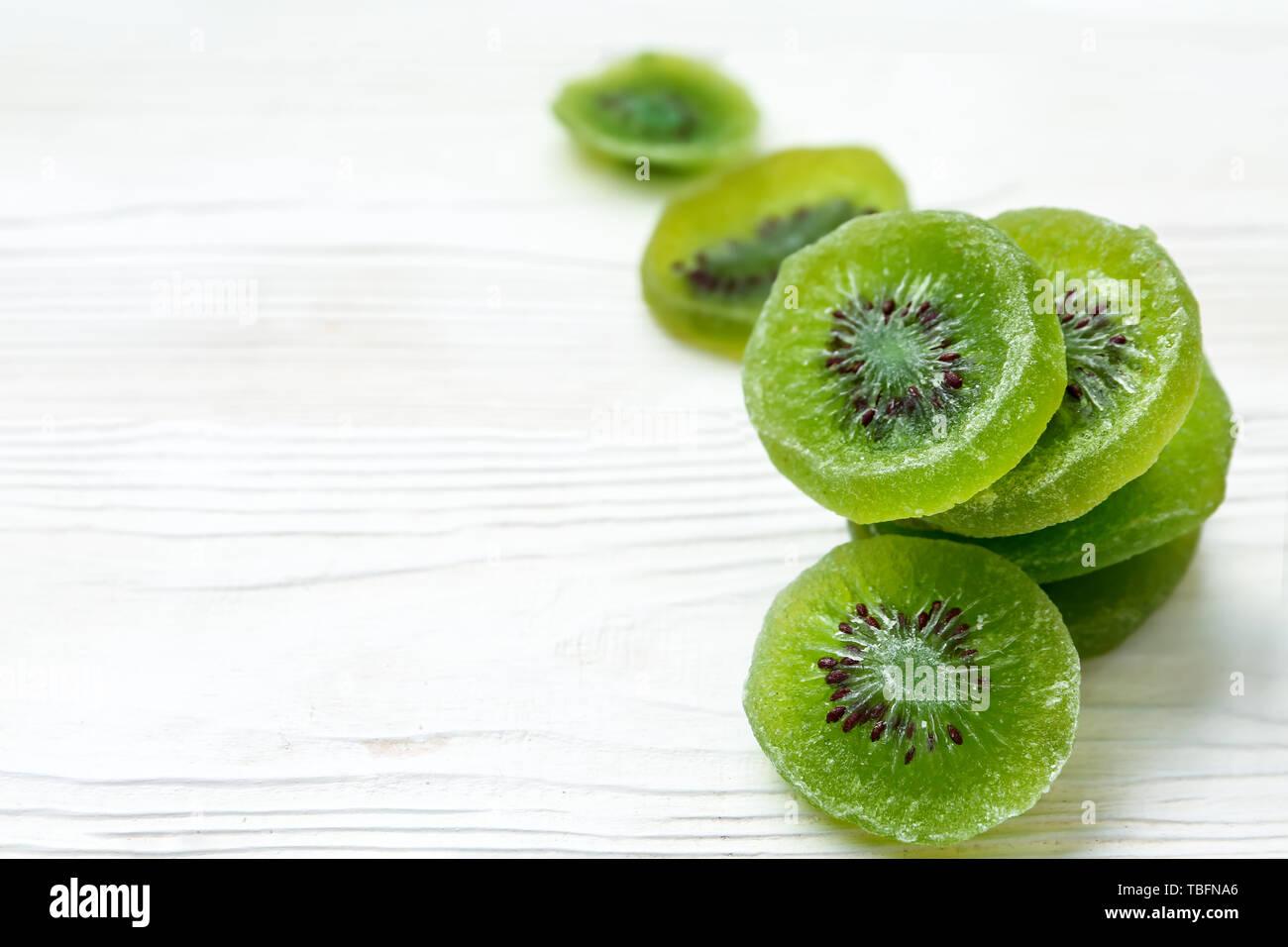 Tasty dried kiwi on white wooden background Stock Photo
