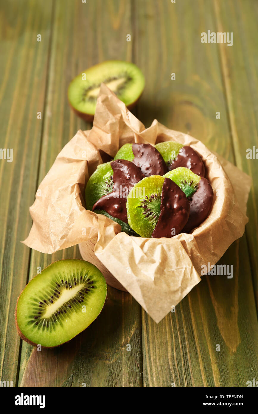 Tasty chocolate covered kiwi on wooden table Stock Photo