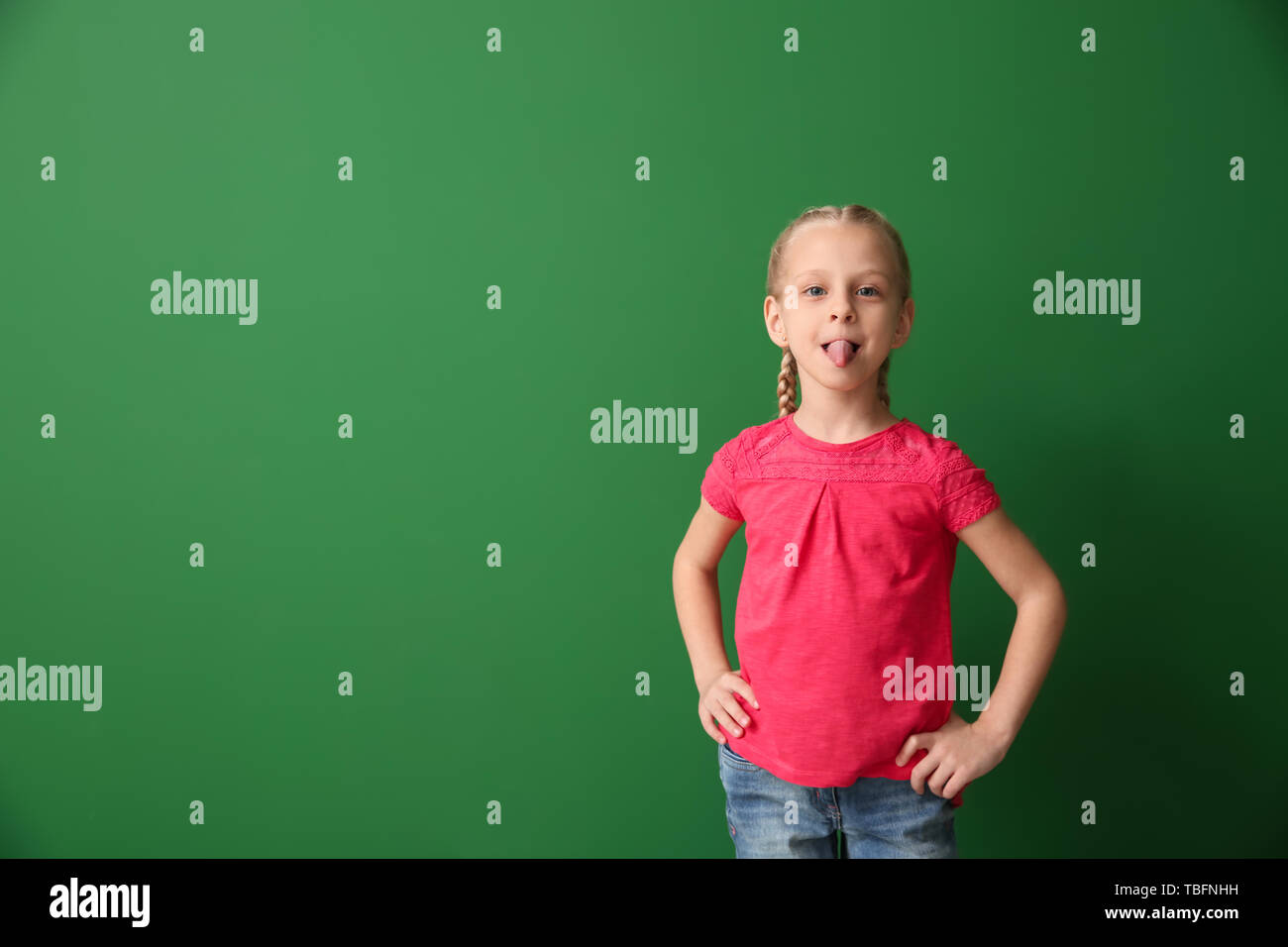 Little girl showing tongue on color background - Stock Image