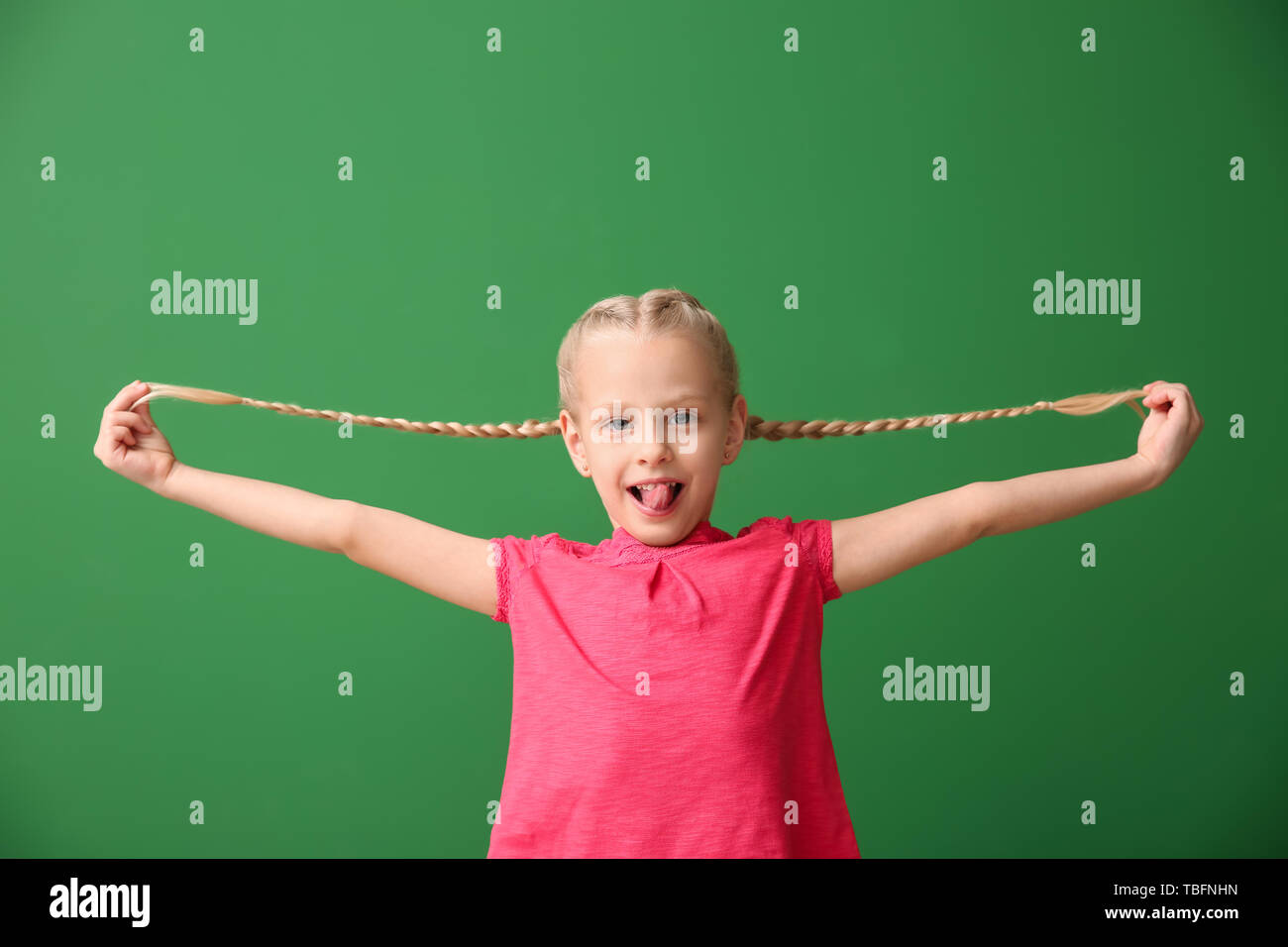 Little grimacing girl on color background - Stock Image