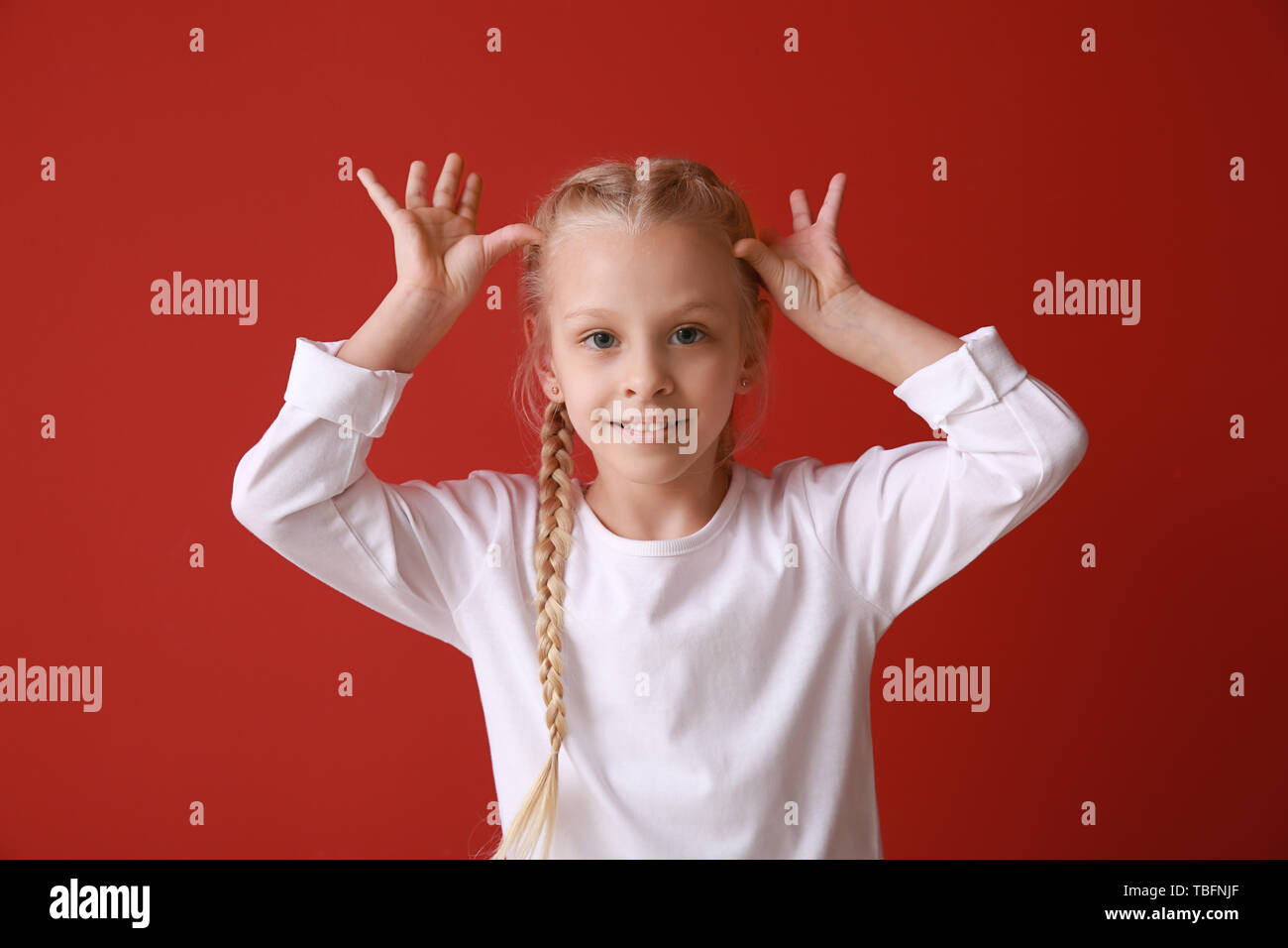 Funny grimacing little girl on color background - Stock Image