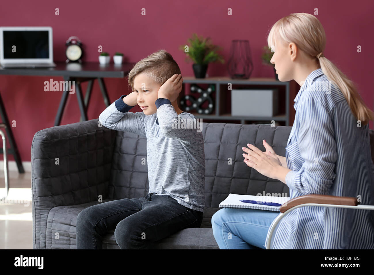 Female psychologist working with naughty little boy in office - Stock Image