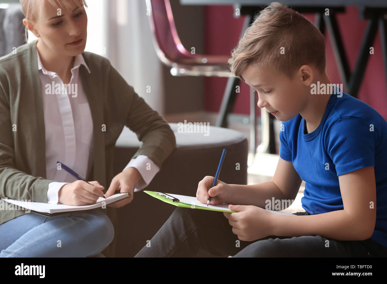 Female psychologist working with little boy in office - Stock Image