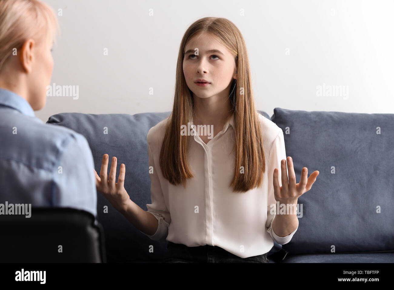 Female psychologist working with teenage girl in office - Stock Image