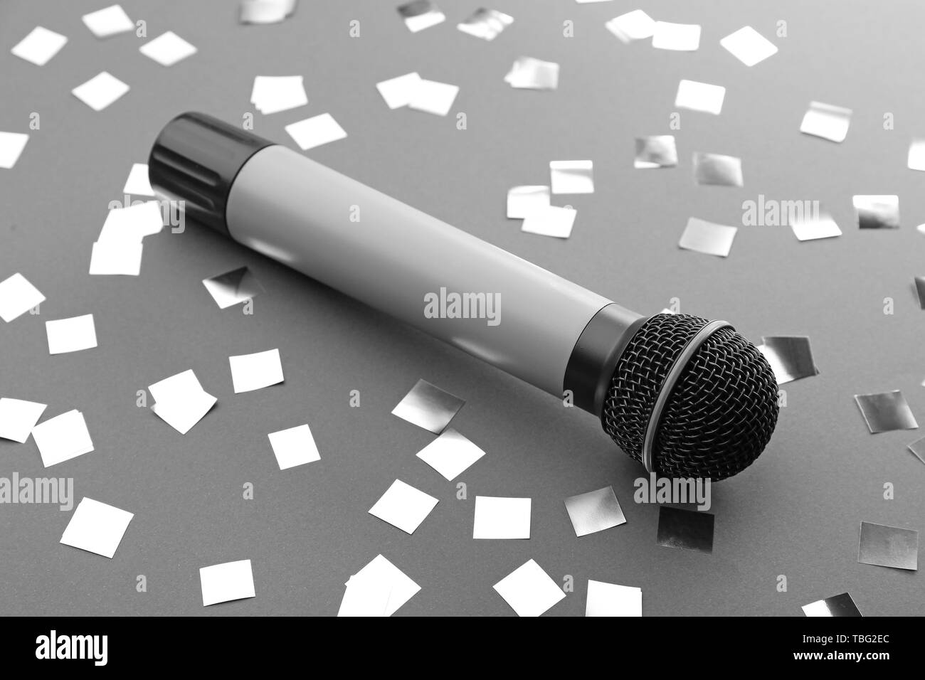 Microphone and confetti on grey background - Stock Image