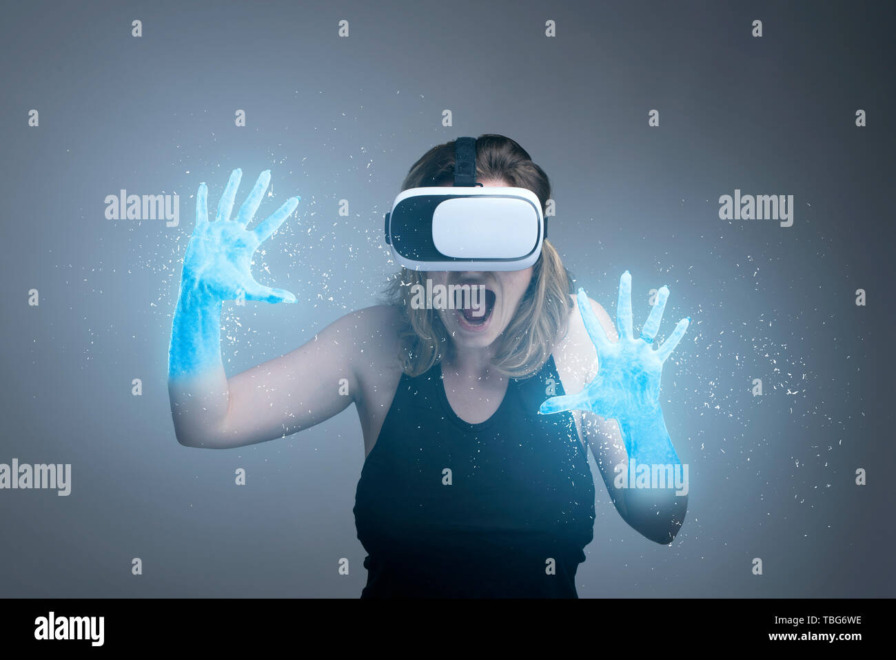 Girl using VR gadget with hands turning into ice in a virtual cyber simulator Stock Photo