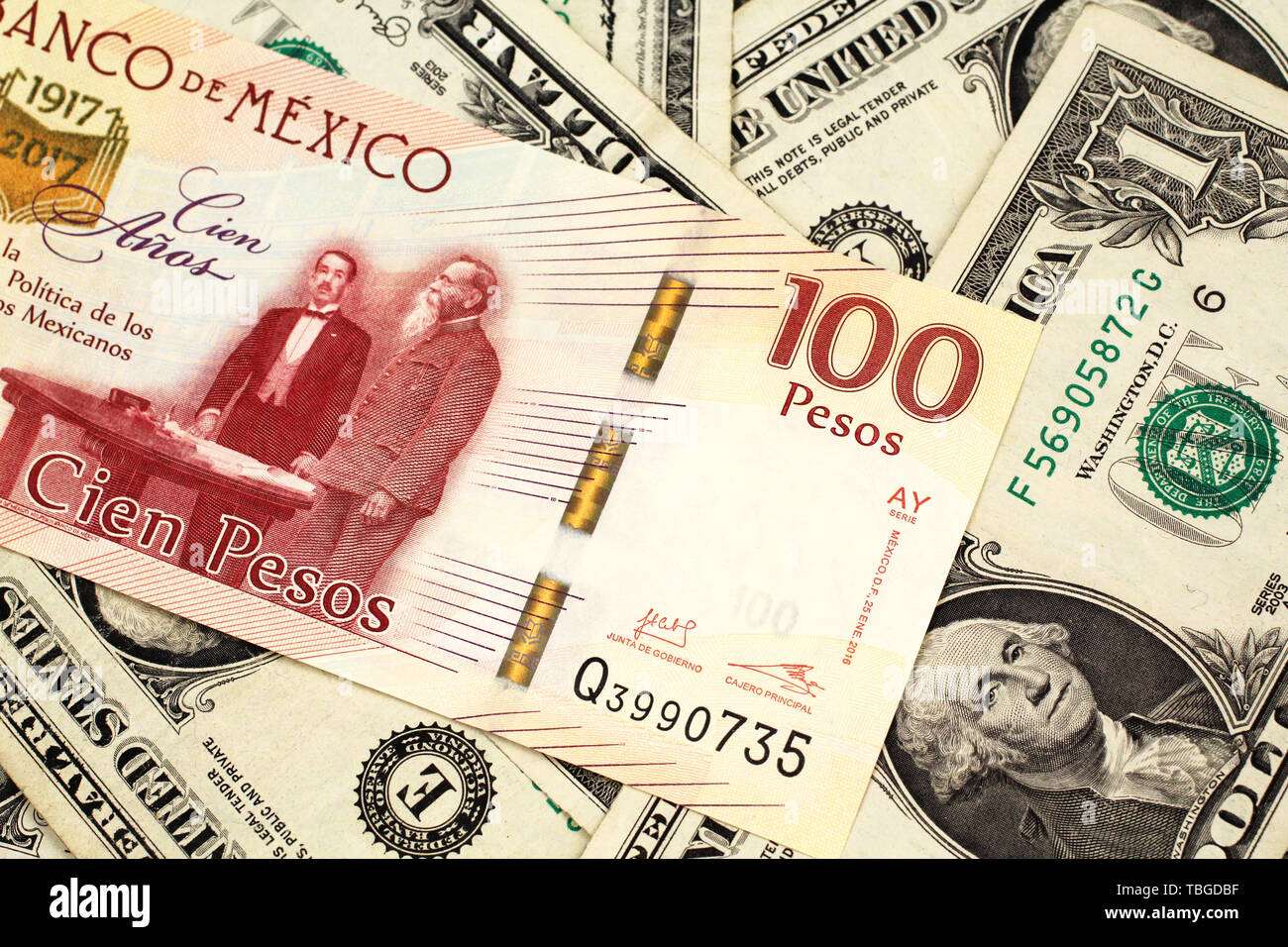 A close up image of a one hundred Mexican peso bank note with American one dollar bills in macro Stock Photo