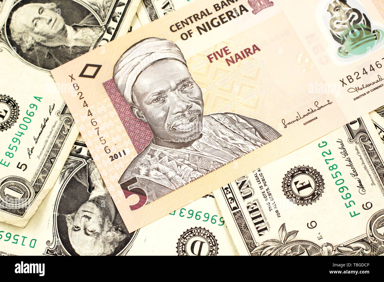 A close up image of a peach colored, five Nigerian naira bank note on a background of American one dollar bills - Stock Image