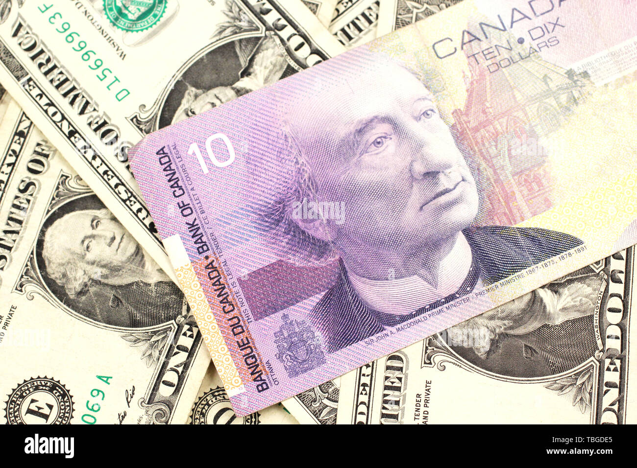 A macro image of a blue Canadian five dollar bill on a background of American one dollar bills close up Stock Photo
