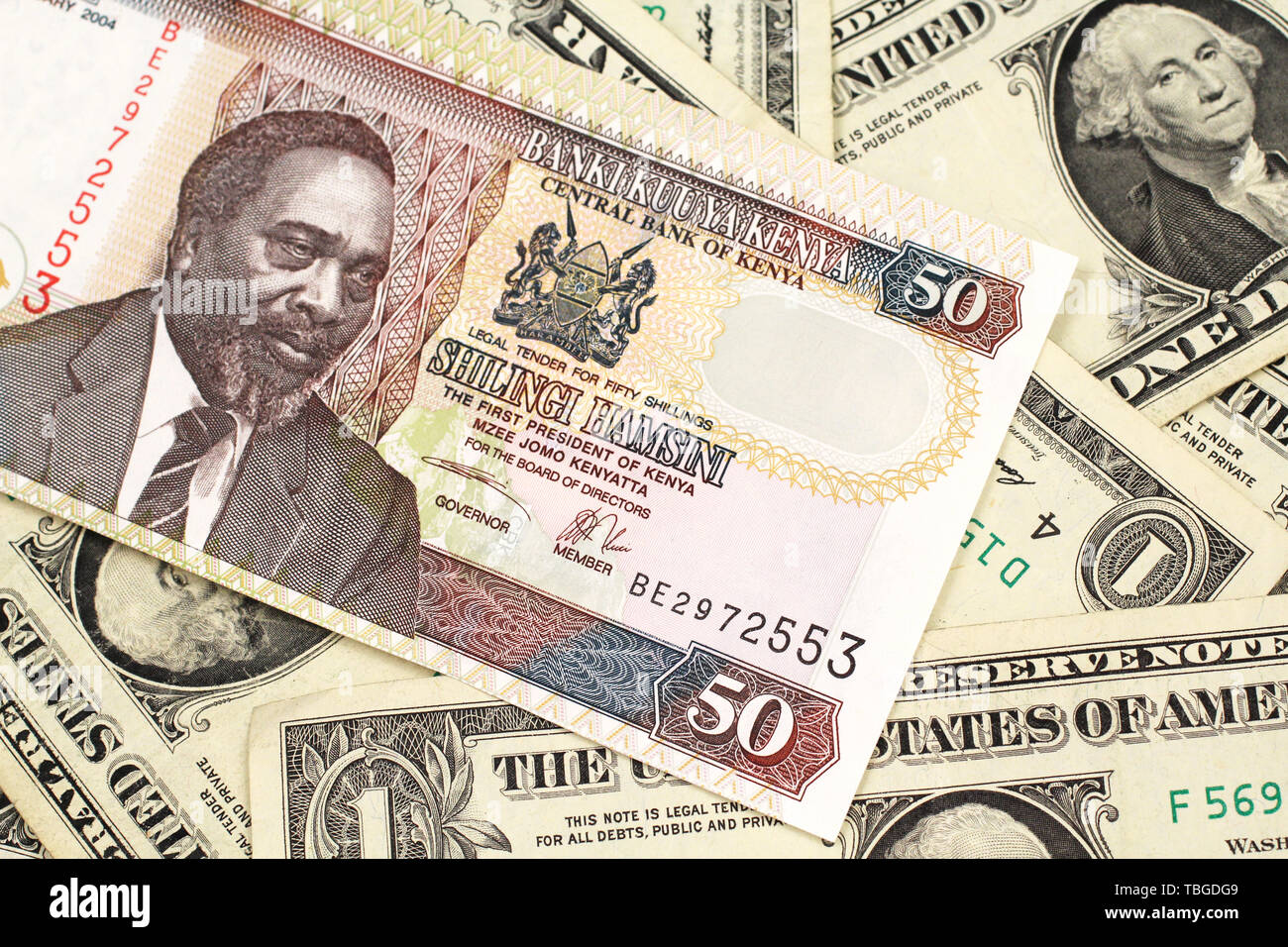A close up image of a fifty Kenyan shilling bank note in macro with American one dollar bills Stock Photo
