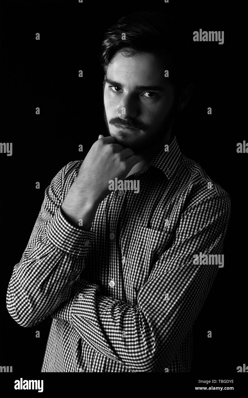 Young adult male looking sinister or contemplative. Monotone, black and white for dramatic effect, dark and moody series. Concept image for corporate  - Stock Image