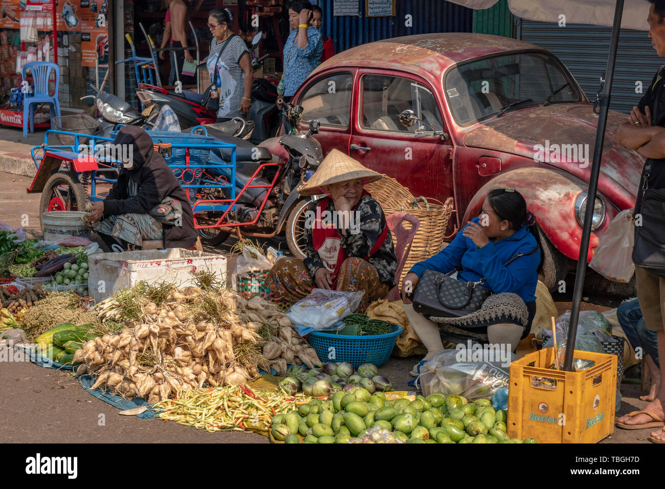 Old women selling fruits and vegetables near Daoheuang Market in Pakse, Laos backgroung VW Beetle, Oldtimer Stock Photo