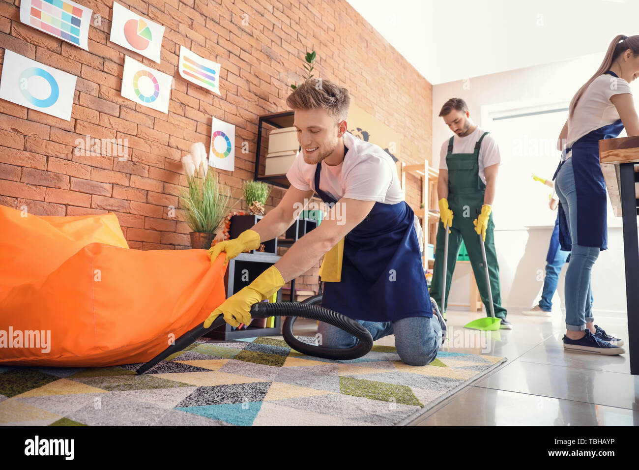 Male janitor cleaning office - Stock Image