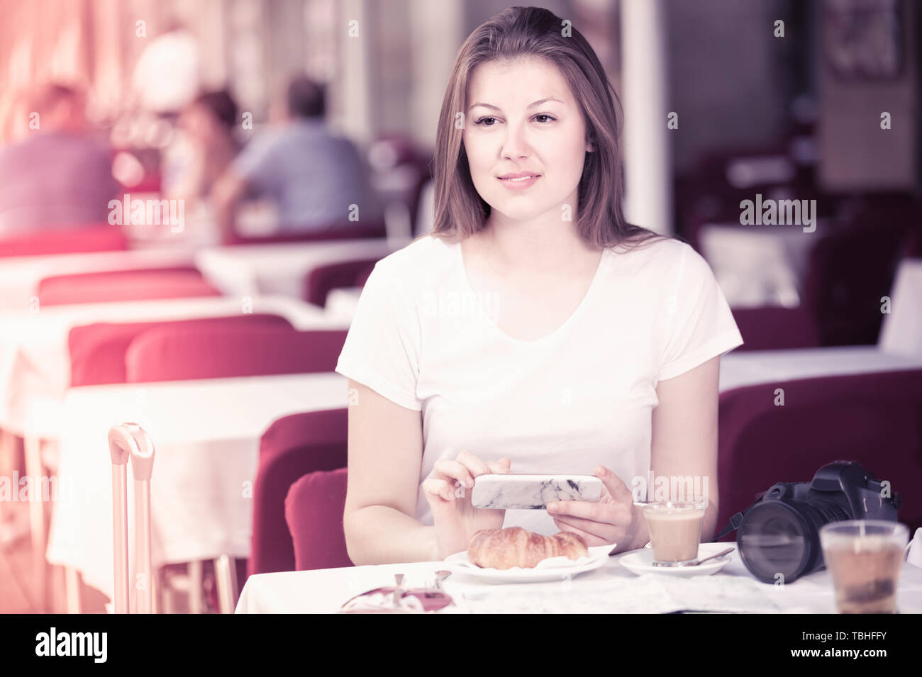 Female-tourist is chatting in the phone in cafee. - Stock Image