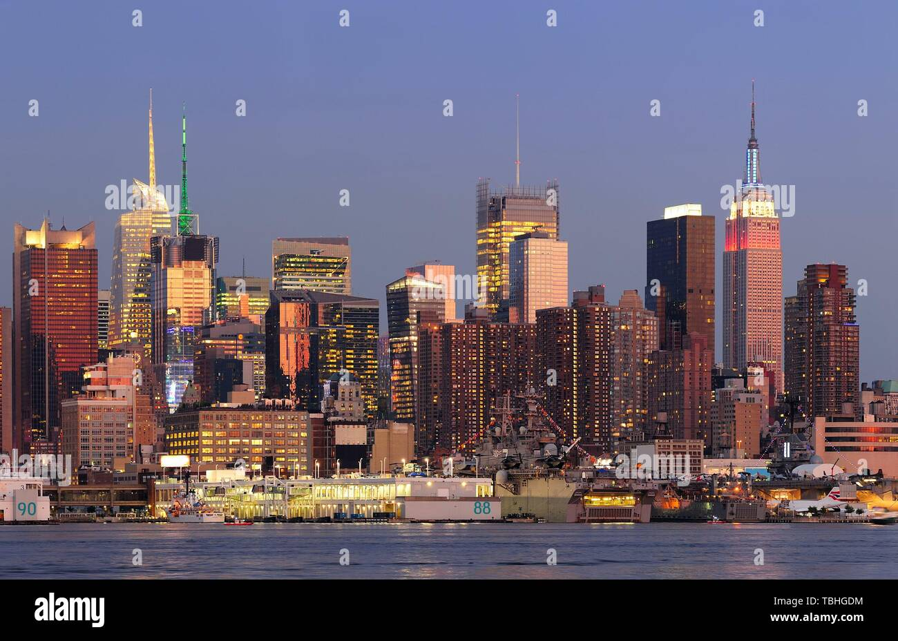 New York City Manhattan sunset panorama with historical skyscrapers over Hudson River with beautiful red color sunshine reflection viewed from New Jersey Weehawken waterfront. Stock Photo