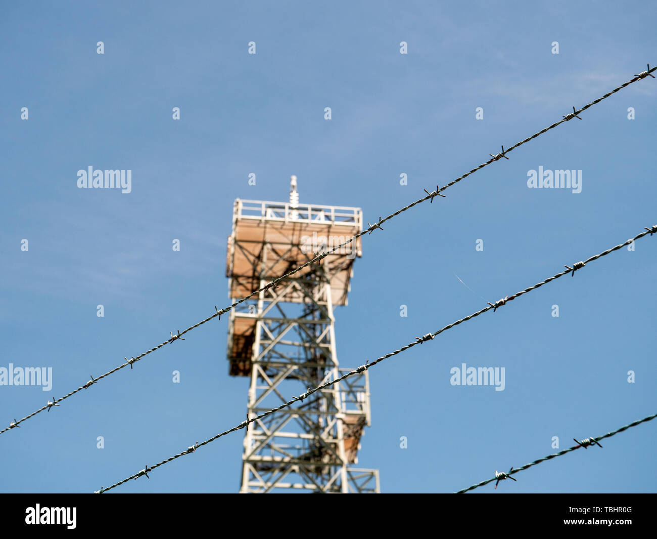 Security fence barber wire in front on surveillance mast clear blue sky Stock Photo