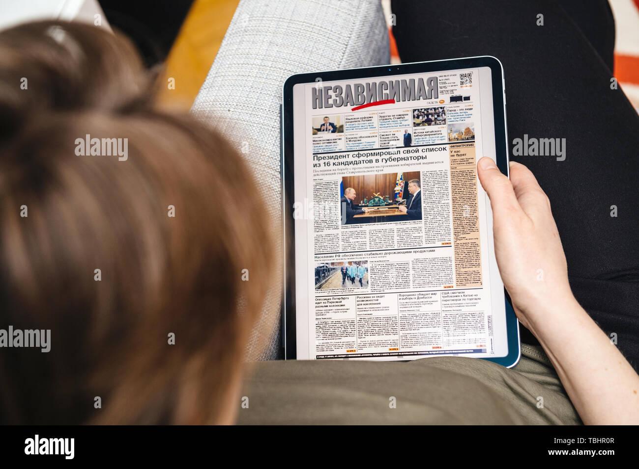 Paris, France - Apr 15, 2019: Woman reading on iPad Pro Apple News Plus Nezavisimaya Gazeta digital newspaper featuring breaking neabout 16 governors list made by Vladimir Putin Russian President - Stock Image