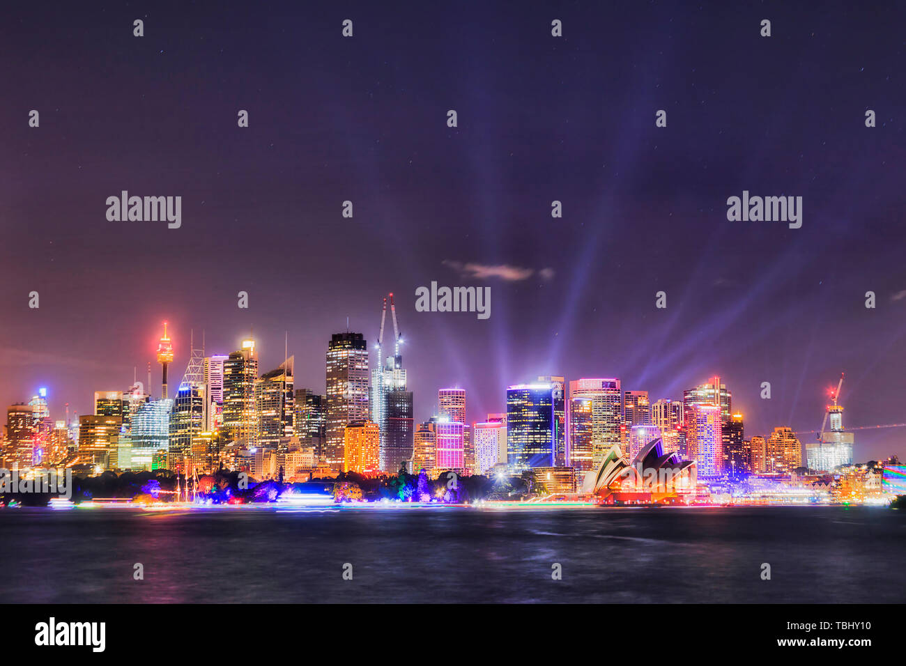 Sydney city CBD on shores of Sydney harbour in bright night time illumination by projected lights during Vivid Sydney light show festival. - Stock Image