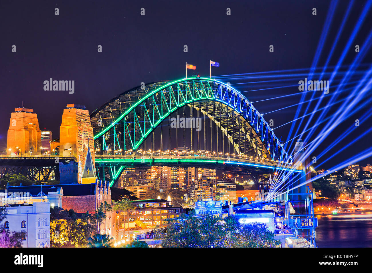 Steel arch of the Sydney Harbour bridge with bright illumination and laser beams in dark night sky over harbour during Vivid Sydney light show. - Stock Image