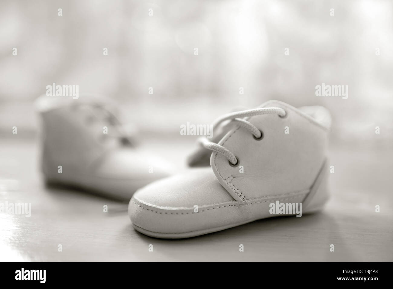 White baby booties made of leather. Shallow depth of field, closeup - Stock Image