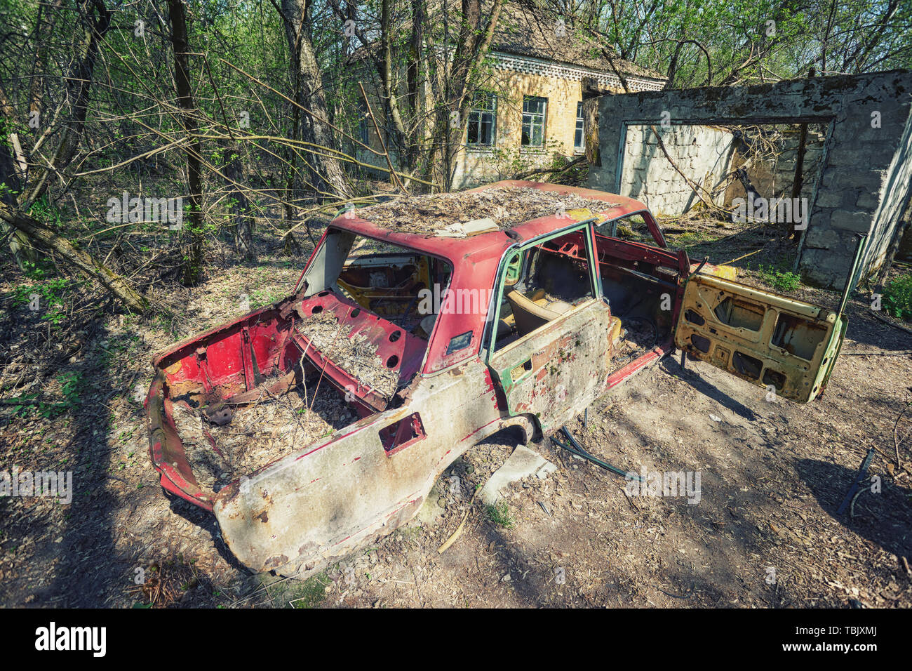 Radioactive dead zone of Chernobyl. Abandoned looted appliances, cars, electronics in Chernobyl accident. Consequences of evacuation, looting and vand - Stock Image