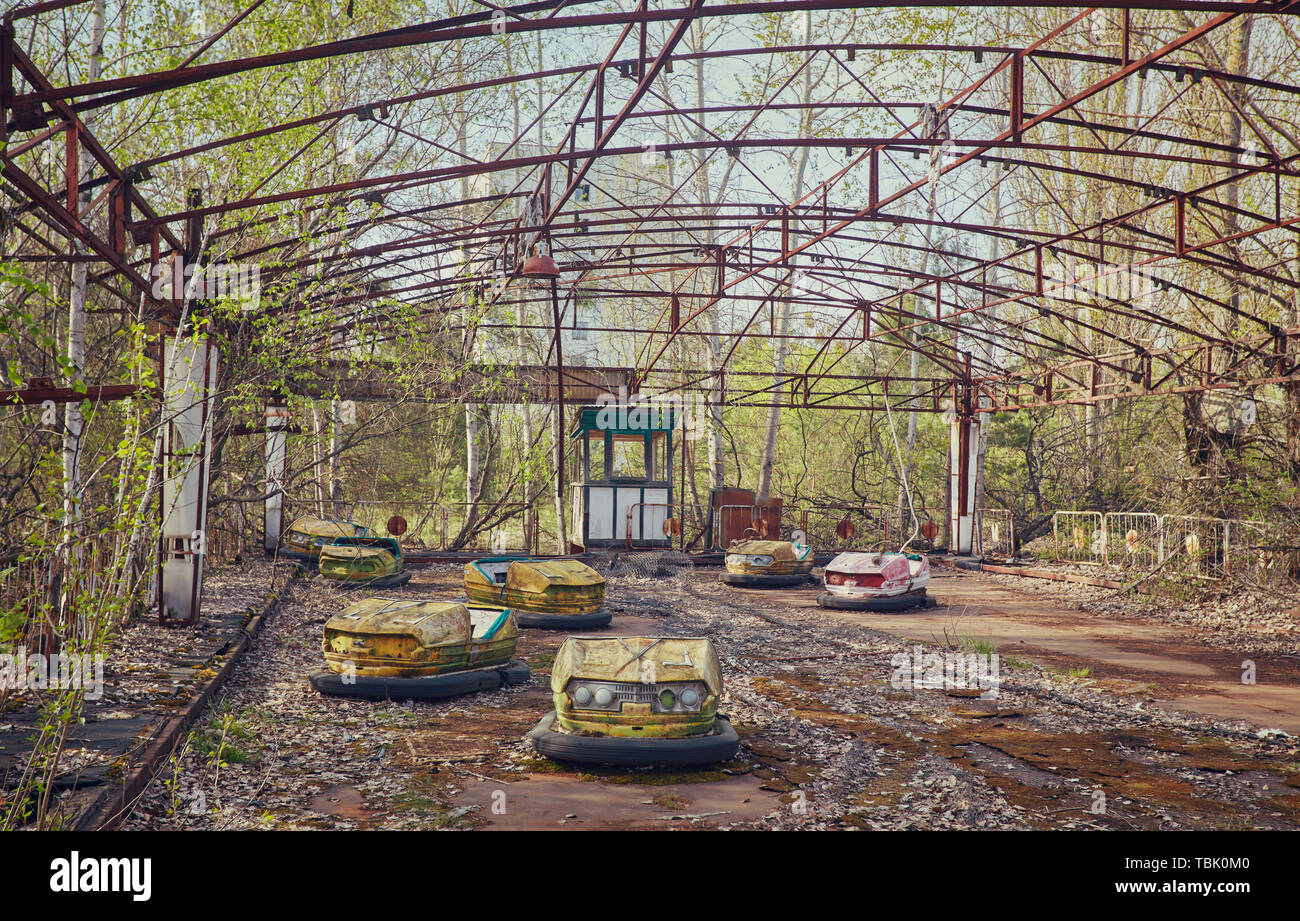 abandoned bumper cars in ruined amusement park in Pripyat city, Exclusion zone of Chernobyl, Ukraine, Eastern Europe Stock Photo