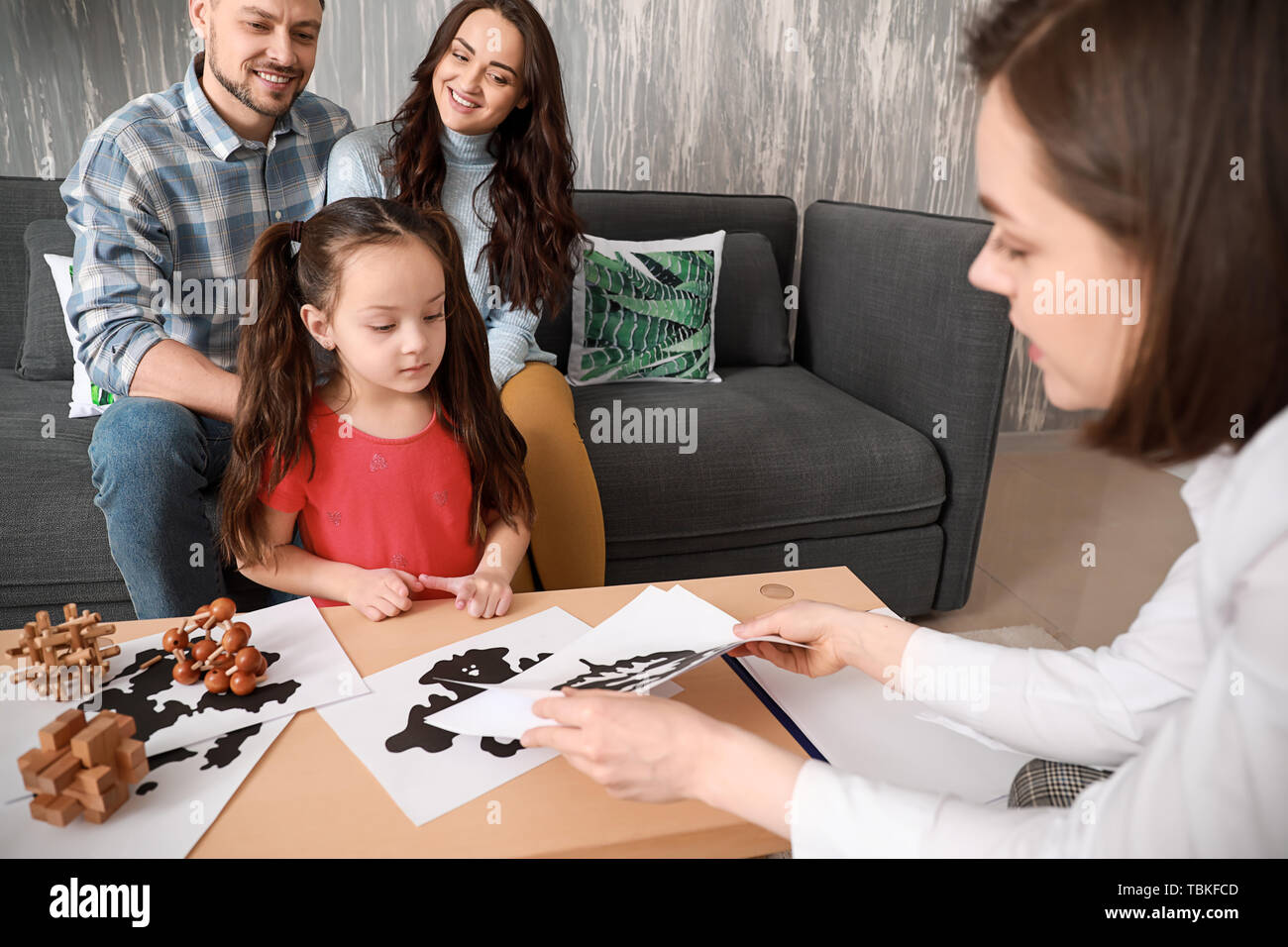 Female psychologist working with family in office - Stock Image