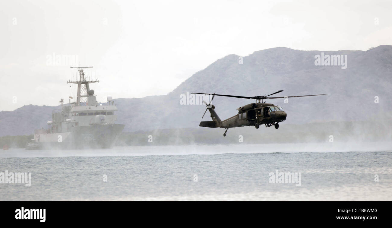 U.S. Army UH-60 Blackhawk flies over Bahia de Las Calderas, Dominican Republic, during helocasting evolutions with partner nations during Tradewinds 2019.  In its 35th year, 22 nations participate in the annual Tradewinds exercise to promote regional security as well as humanitarian assistance and disaster relief. (U.S. Army photo by Sgt. Leia D. Tascarini) - Stock Image