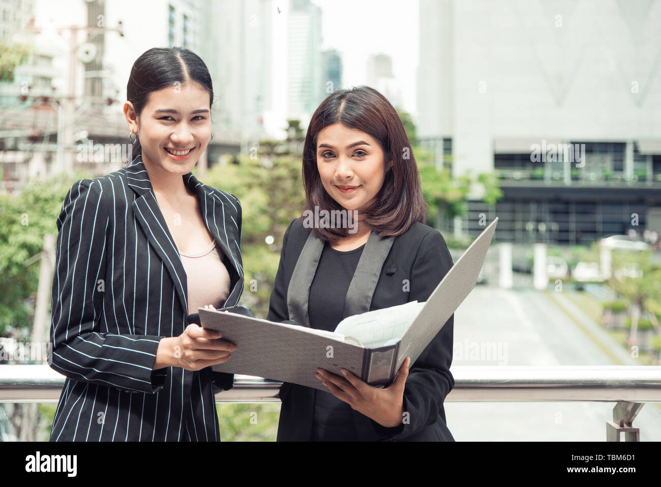 Two young Asian businesswomen looking into document file folder for analyzing profit or sale break even point after marketing. Business teamwork emplo - Stock Image