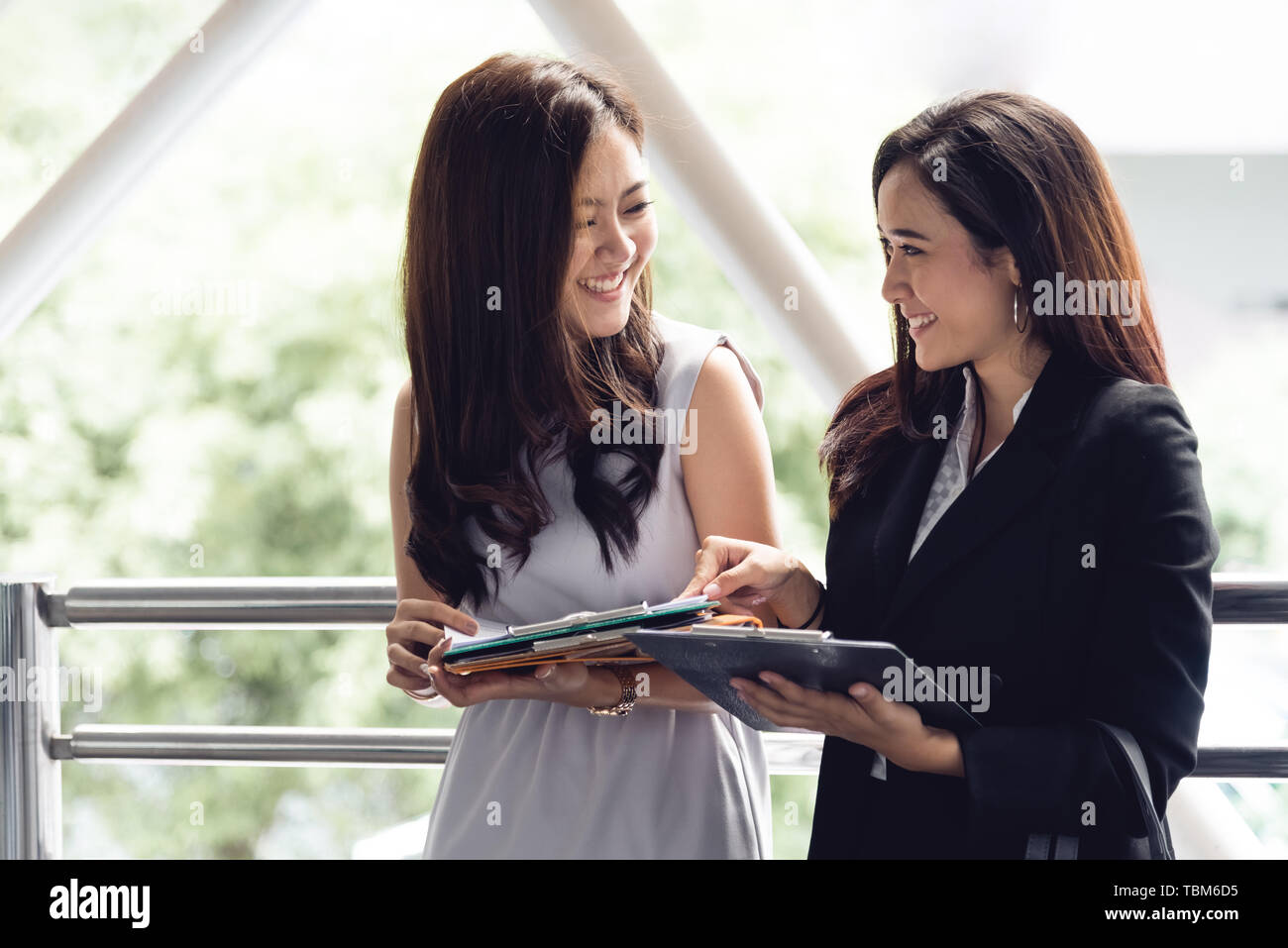 Two happy young Asian businesswomen looking into document file folder for analyzing profit or sale break even point after marketing. Business teamwork - Stock Image